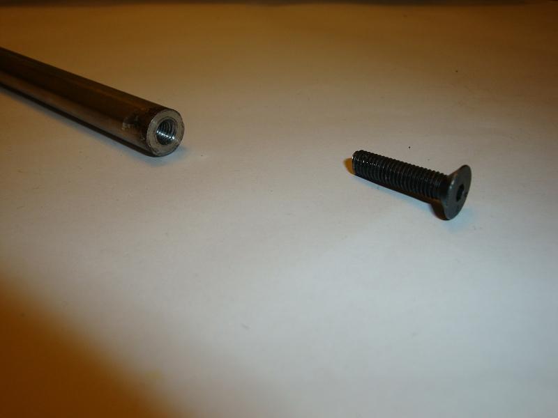 Gebohrter Stab mit Gewinde und passender Schraube